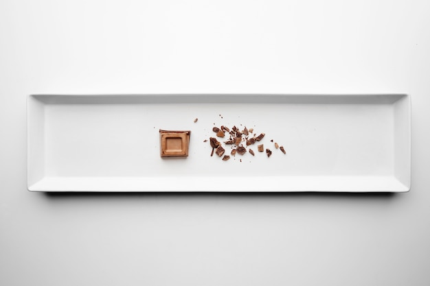 Kawałek czekolady i kruszonki na białym tle w środku prostokątny talerz ceramiczny na tle białego stołu
