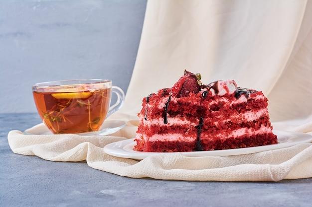 Kawałek czerwonego aksamitnego ciasta na białym talerzu z herbatą.