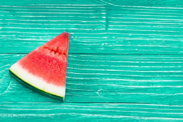 Kawałek czerwony soczysty arbuz na zielonym tle