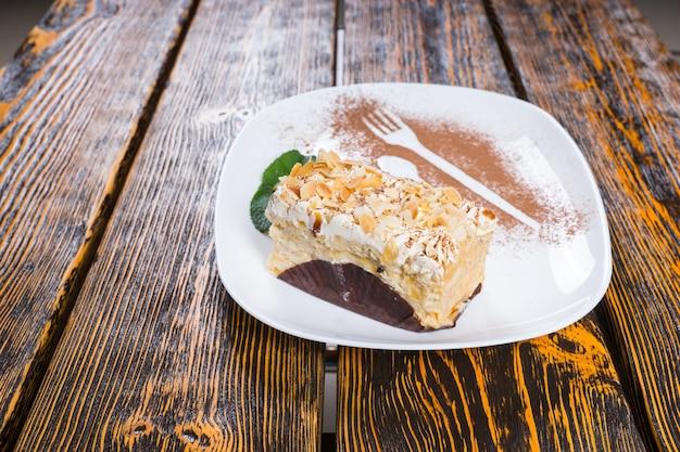 Kawałek dekadenckiego kremowego ciasta zwieńczony orzechami podany na białym półmisku i przyozdobiony listkami mięty i posypką kakaową na powierzchni drewnianego stołu