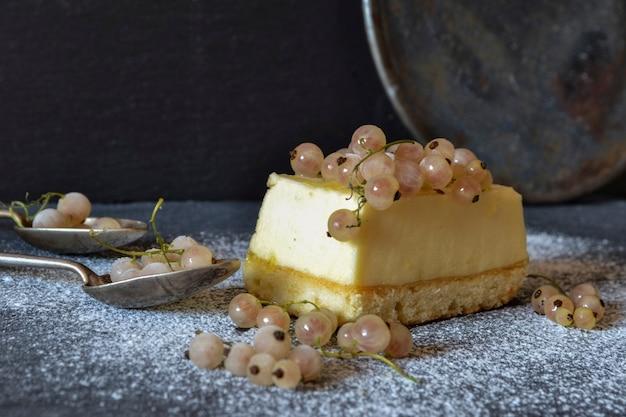 Kawałek deseru sernik z jagód świeżych porzeczek na ciemnym tle. przedni widok.