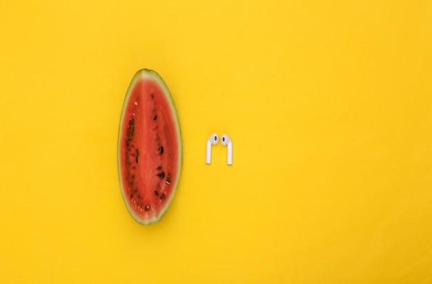 Kawałek dojrzałego arbuza i bezprzewodowe słuchawki na żółtym tle. letnia zabawa. widok z góry. płaskie ułożenie