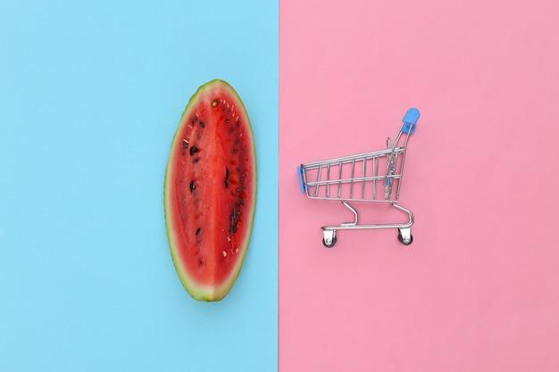 Kawałek dojrzałego arbuza i mini wózek na zakupy na różowym niebieskim tle. letnia zabawa. widok z góry. płaskie ułożenie