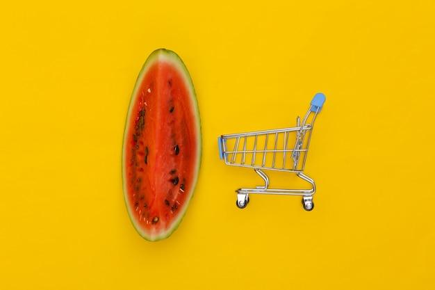 Kawałek dojrzałego arbuza i mini wózek na zakupy na żółtym tle. letnia zabawa. widok z góry. płaskie ułożenie