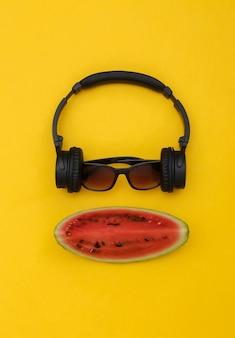 Kawałek dojrzałego arbuza i słuchawki stereo z okularami przeciwsłonecznymi na żółtym tle. letnia zabawa. widok z góry. płaskie ułożenie