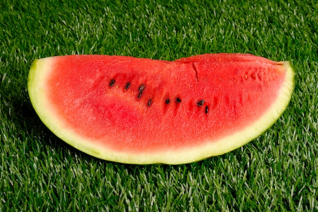 Kawałek dojrzałego soczystego arbuza leży na zielonej trawie z bliska, piknik.