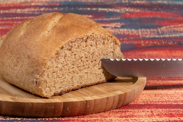 Kawałek domowego chleba pokrojony na bambusowej tacy na rustykalnym stole