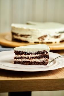 Kawałek domowego ciasta czekoladowego na talerzu. drewniane tło