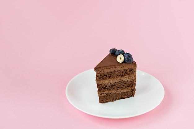 Kawałek domowego ciasta czekoladowego z jagodami i orzechami na talerzu na różowym tle