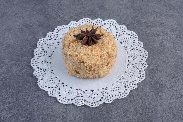 Kawałek domowego ciasta ozdobiony goździkami na marmurowej powierzchni.