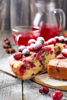 Kawałek domowego ciasta żurawinowego z orzechami włoskimi, jagodami i cukrem pudrem na starym drewnianym fone. miejsce na tekst. styl rustykalny. selektywna ostrość.