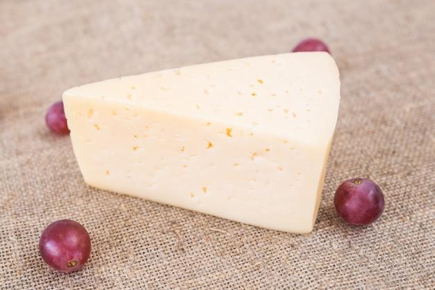 Kawałek domowego sera i winogron, widok z góry.