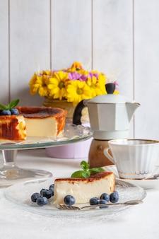 Kawałek domowego sernika spalonego baskijskiego na talerzu z jagodami i listkami mięty na jasnej powierzchni, filiżanka kawy, gejzer, bukiet żółtych kwiatów.