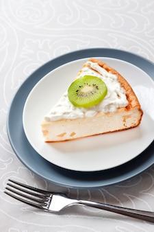 Kawałek domowego twarożku z owocami kiwi i śmietaną na talerzu