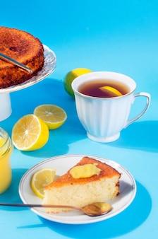 Kawałek domowej roboty świeżo upieczony biszkopt na talerzu, lemon kurd w szklanym słoju z łyżką, całe i pokrojone świeże cytryny na talerzu na niebieskim tle z cieniami. skopiuj miejsce. ostre światło