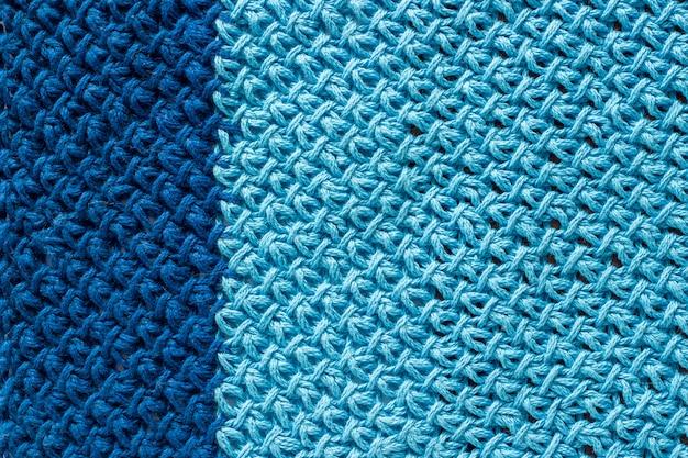 Kawałek dwukolorowej niebieskiej dzianiny, tła lub tekstury. przędza dziewiarska ręcznie