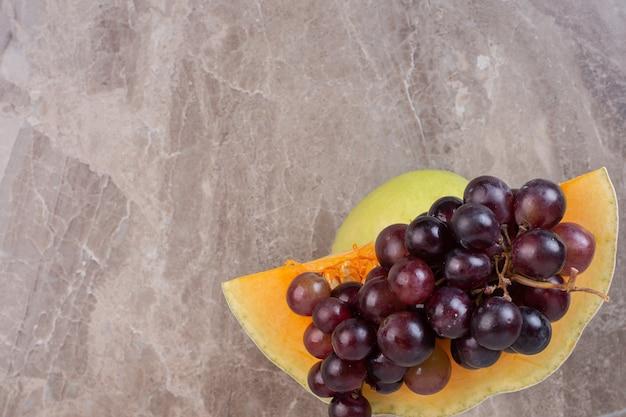 Kawałek dyni i winogron na marmurowej powierzchni.