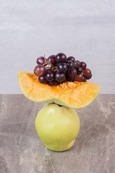 Kawałek dyni, pigwy i winogron na marmurowym stole.