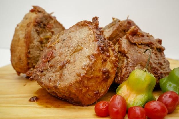 Kawałek garnka gotowanego mięsa na drewnianej desce z nożem i sztućcami