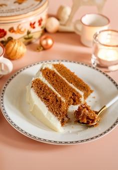 Kawałek glazurowanego tortu marchewkowego na białym talerzu z sezonowym tłem boże narodzenie.