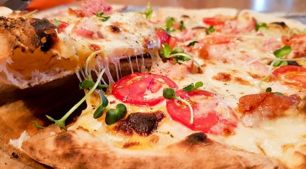 Kawałek gorącej pizzy, duży ser, obiad lub kolacja, skorupa z owoców morza, sos mięsny. z warzywami papryki smaczne pyszne fast food włoskie tradycyjne na drewnianym stole klasyczny widok z boku.