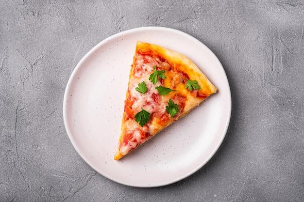 Kawałek gorącej pizzy z serem mozzarella, szynką, pomidorem i pietruszką na talerzu
