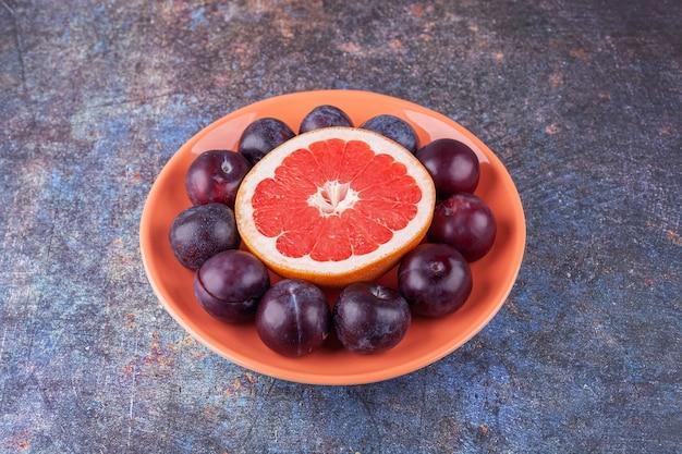 Kawałek grejpfruta z pysznymi śliwkami umieszczony na pomarańczowym talerzu.