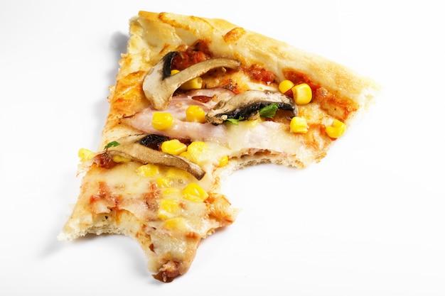 Kawałek gryźć daleko pizza odizolowywająca na bielu. fast food, koncepcja fast foodów. mięso, świeże