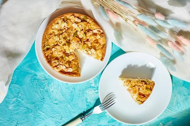Kawałek jabłka lub gruszki, tarta z karmelowymi orzechami na niebieskim stole w świetle słonecznym