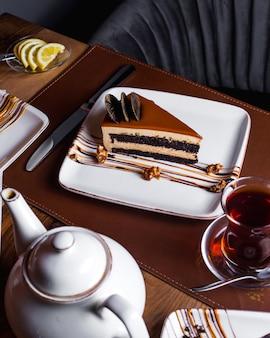 Kawałek karmelowego ciasta ozdobiony czekoladowymi ciasteczkami podawany z herbatą