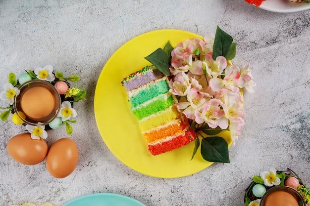 Kawałek kolorowego ciasta i brązowe jajka na przyjęcie wielkanocne.
