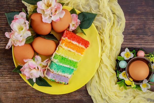 Kawałek kolorowego ciasta i brązowe jajka na przyjęcie wielkanocne
