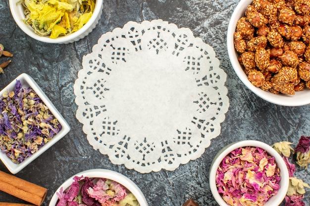 Kawałek koronki i miseczki z suchymi kwiatami i orzechami wokół niego na szarym podłożu