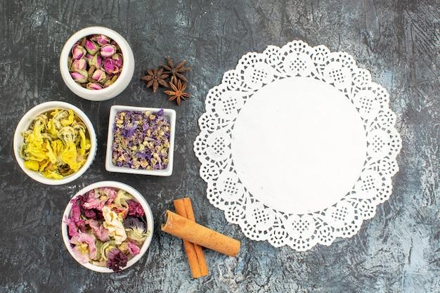 Kawałek koronki z miseczkami z suchych kwiatów na szaro