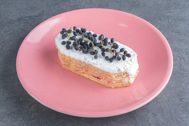 Kawałek kremowego ciasta czekoladowego na różowym talerzu