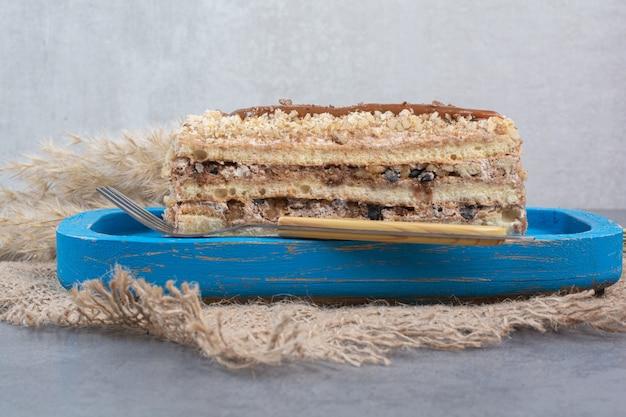 Kawałek kremowego ciasta na niebieskim talerzu widelcem.