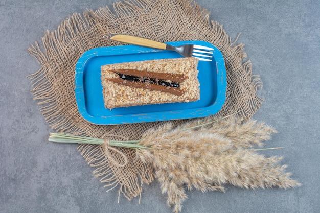 Kawałek kremowego ciasta na niebieskim talerzu widelcem