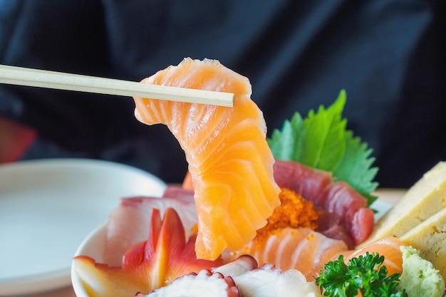 Kawałek łososia pałeczkami, miska ryżu sashimi chirashi don japońskie jedzenie