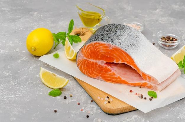 Kawałek łososia z czerwonej ryby z cytryną, oliwą, świeżą bazylią i przyprawami