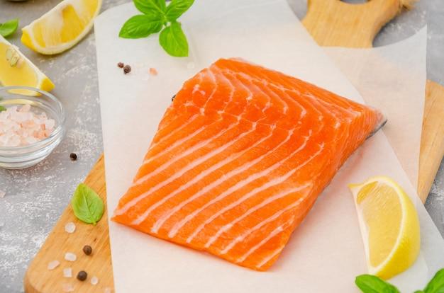 Kawałek łososia z czerwonej ryby z cytryną, oliwą z oliwek, świeżą bazylią i przyprawami