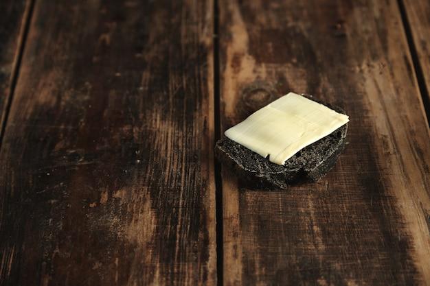 Kawałek luksusowego domowego chleba z czarnym węglem drzewnym i masłem na białym tle na rustykalnym drewnianym stole
