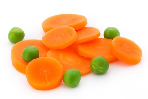 Kawałek marchwi, zielony groszek, na białym tle