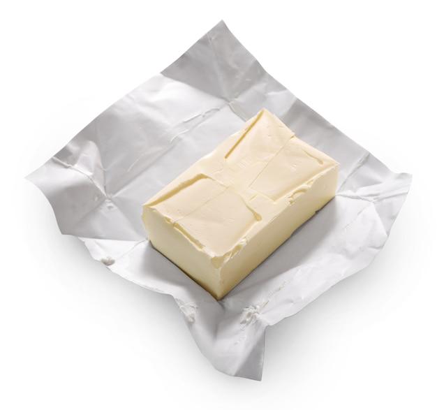 Kawałek masła na białym tle