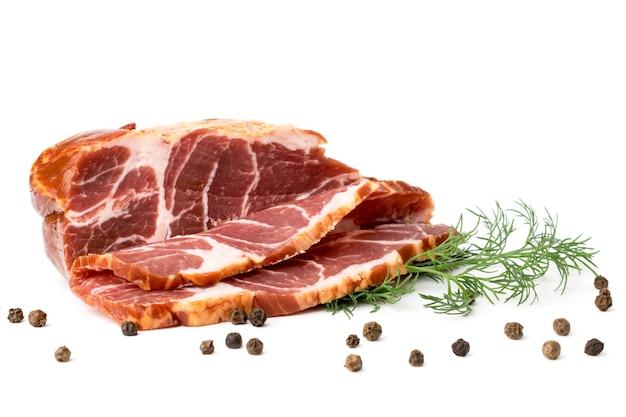 Kawałek mięsa karkówki pokrojone z czarnym pieprzem i koperkiem pozostawia na białym tle.