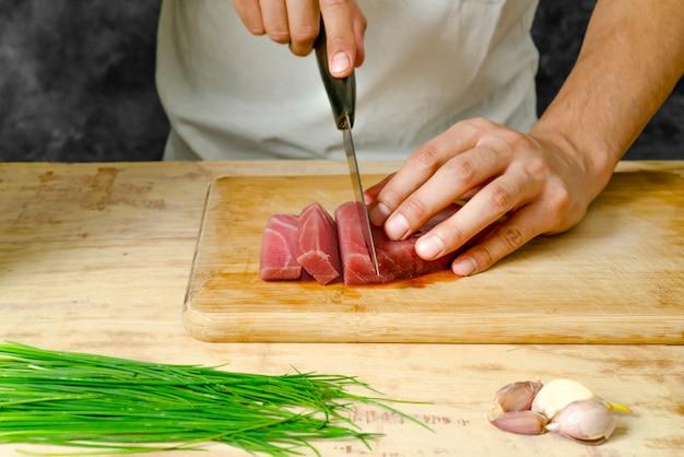 Kawałek mięsa z tuńczyka na desce i ręcznie krojąc go nożem