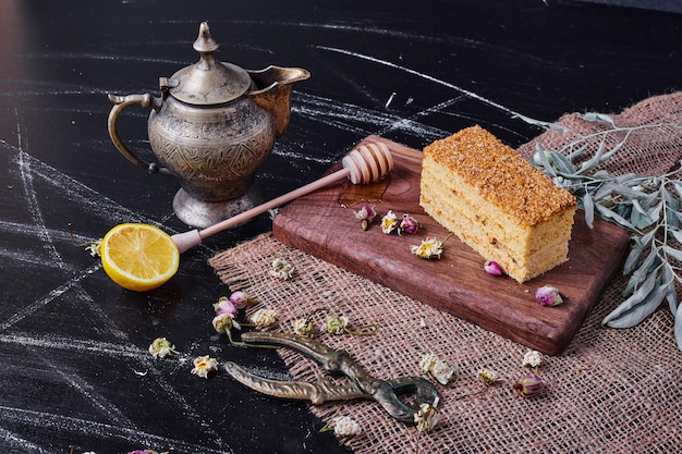 Kawałek miodowego ciasta z suszonymi kwiatami na marmurowym stole.