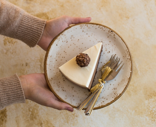 """Kawałek musu """"trzy czekoladowe"""" w ręku dziewczyny, posypany startą czekoladą i ozdobionym cukierkiem"""