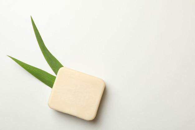 Kawałek naturalnego mydła i liści na białym tle