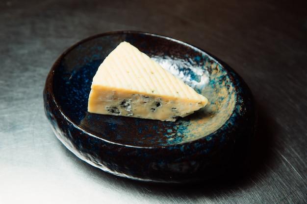 Kawałek niebieskiego sera leży na talerzu, gotowy do podania.