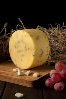 Kawałek okrągłego żółtego twardego sera z pestkami słonecznika, sianem, gałązkami czerwonych i zielonych winogron na widoku z boku deski do krojenia